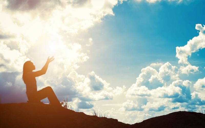 Silhouette of woman praying over beautiful sunrise background